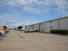 Commercial warehouse buildings with concrete parking & sidewalks